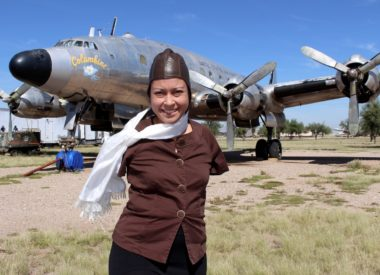 Jessica Cox in front of airplane in pilot gear