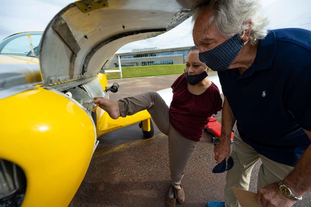 Jessica and Senator Harking preflighting the Ercoupe airplane